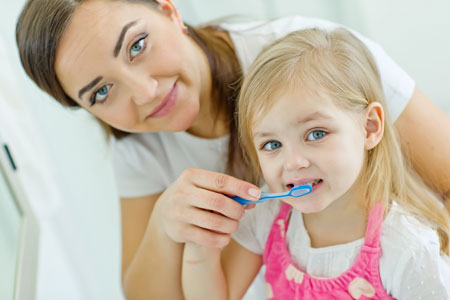 Mom and Daughter brushing their teeth - Pediatric Dentist and Orthodontist Dr. Steven Marcello